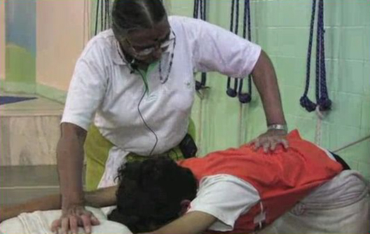 Geeta Iyengar with her hand on a student's back, the student is lying down