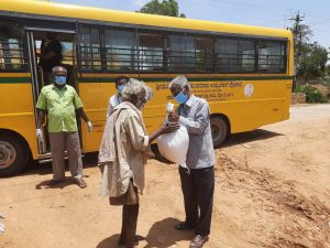 man receiving an emergency food package in front of a yellow bus
