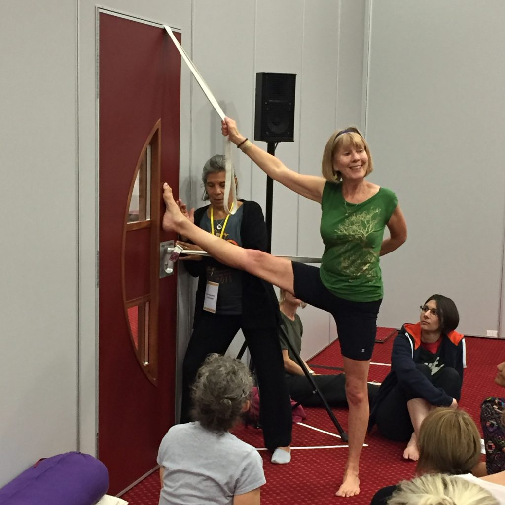 Teacher using a door to support her leg and arm in a yoga pose